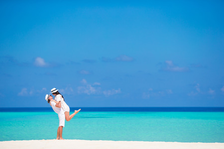 Young happy couple on white beach at summer vacation Stock Photo