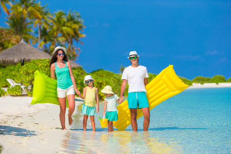 adult sisters: Happy beautiful family on white beach with inflatable air mattresses and toys