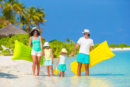 family holidays: Happy beautiful family on white beach with inflatable air mattresses Stock Photo