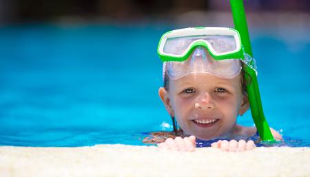 natacion: Niña adorable en la máscara y gafas de buceo en piscina al aire libre