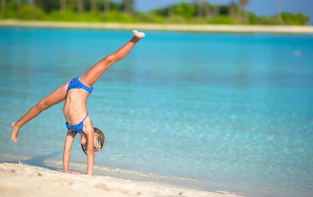 gimnasia: Ni�a adorable que se divierten haciendo voltereta en la playa de arena blanca tropical Foto de archivo