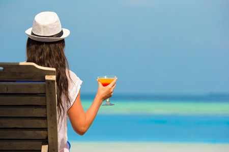 Young woman with cocktail glass near swimming pool photo