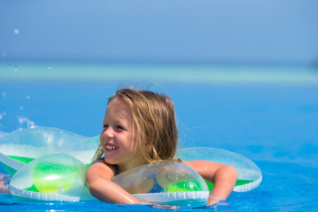 swimming goggles: Little happy cute girl in outdoor swimming pool