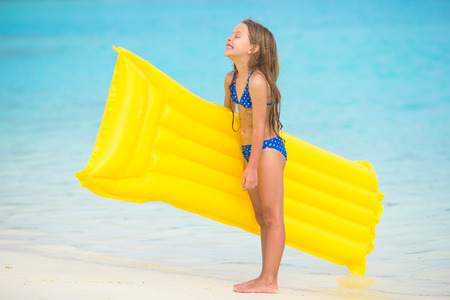 Adorable happy girl with inflatable air mattress on white beach photo