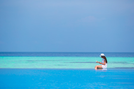 water  scenic: Young girl reading book near swimming pool