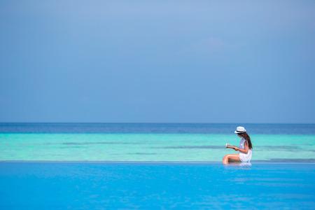 swimming pool water: Young girl reading book near swimming pool