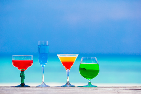 Four colorful exotic tasty cocktails background turquoise sea photo