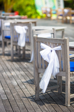 wedding chairs: Wedding chairs decorated with white bows at outdoor cafe