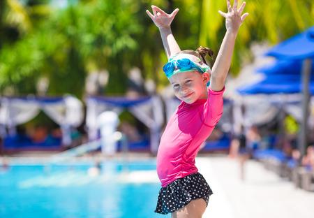 Happy beautiful girl having fun in outdoor swimming pool photo