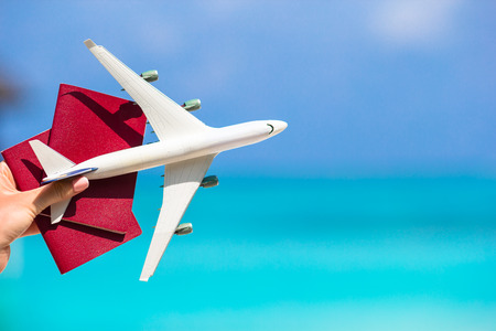 Closeup of passports and white airplane background the sea Foto de archivo