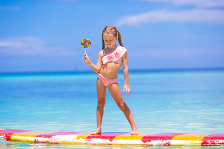 surf girl: Little girl with lollipop have fun on surfboard in the sea