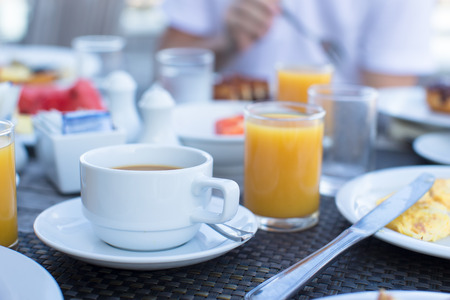 breakfast hotel: Delicious tasty cappuccino and fresh juice for breakfast at outdoor cafe