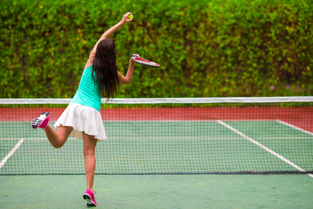 Young sportswoman playing tennis on tropical vacation photo