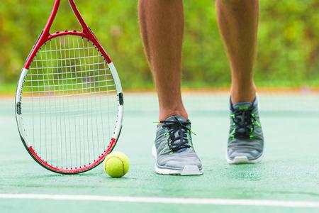 tenis: Close up de zapatillas de deporte cerca de la raqueta de tenis y pelota