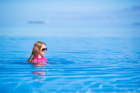 Smiling adorable girl having fun in outdoor swimming pool photo