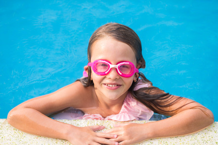 Smiling happy girl in goggles for swimming at outdoor pool photo
