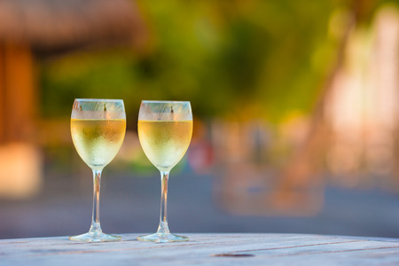 chardonnay: Two glasses of tasty white wine at sunset