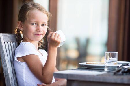 honey blonde: Little adorable girl drinking tea on breakfast in outdoor cafe Stock Photo