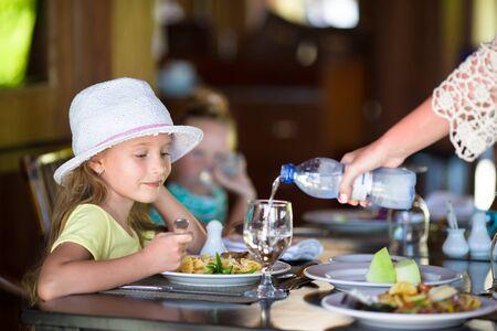 honey blonde: Adorable little girl having dinner at outdoor restaurant
