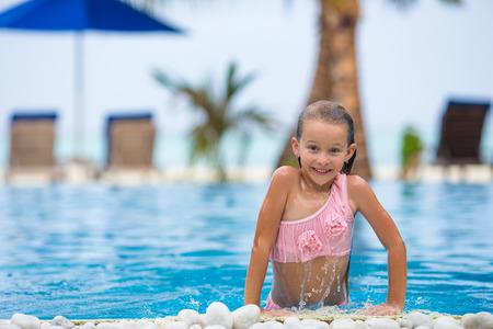 Smiling happy beautiful girl having fun in outdoor swimming pool photo
