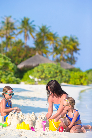 Mother and two kids playing with sand on tropical beach photo
