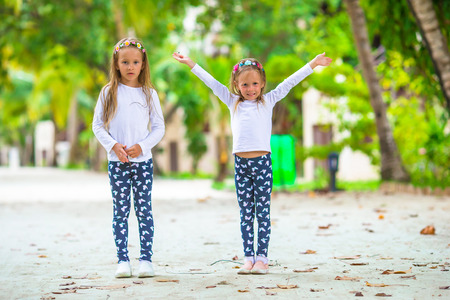 Adorable little girls having fun during beach vacation photo