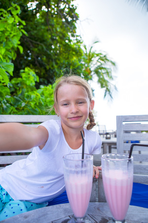 Little girls taking selfie and drinking tasty cocktails at tropical resort photo