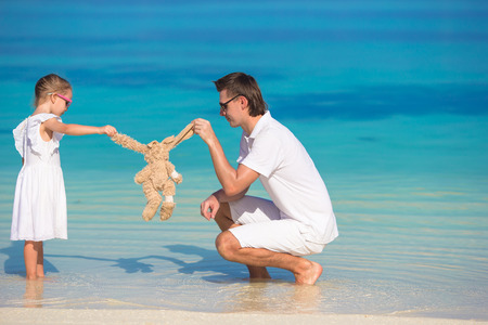 Dad and little girl with plush toy during summer vacation photo
