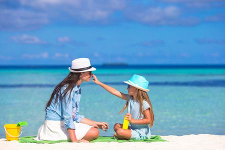 little girl beach: Little adorable girl applying sun cream to her mother nose