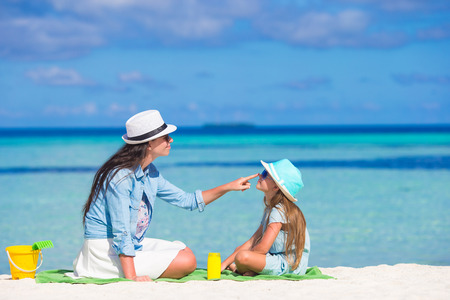 Mother applying sun protection cream to her daughter at tropical beach 版權商用圖片 - 39253378