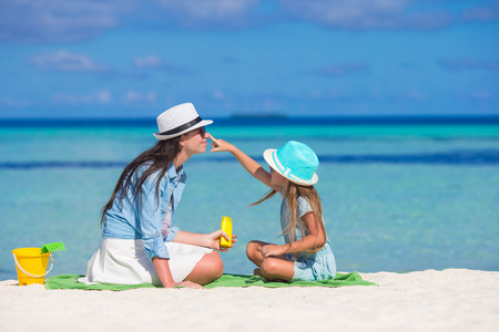 Little girl applying sun cream to her mother nose
