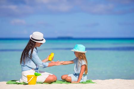 Jonge moeder aanbrengen van zonnebrandcrème op haar kind
