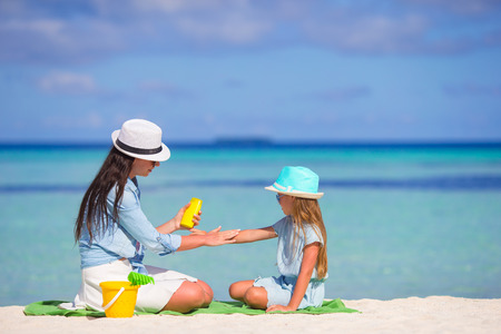 Young mother applying sunscreen on her kid photo