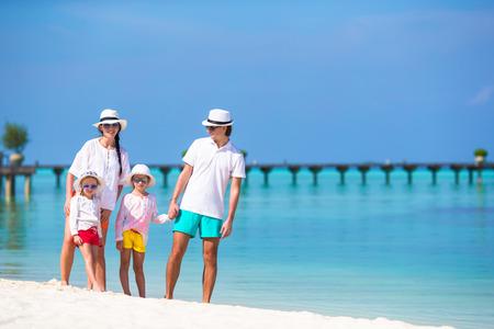 familias jovenes: La familia feliz durante vacaciones en la playa