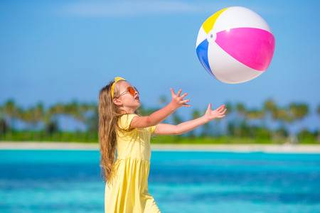 ball: Little adorable girl playing on beach with ball