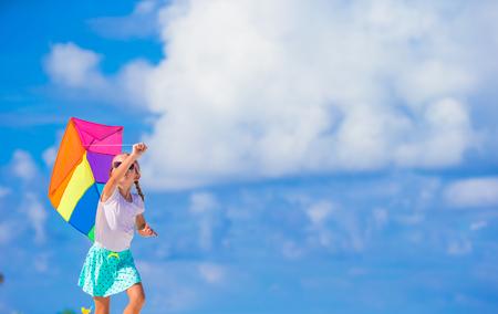 papalote: Ni�a feliz jugando con la cometa volando en la playa tropical