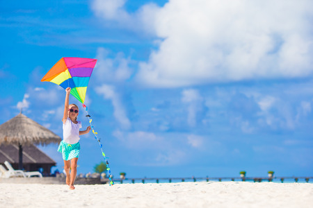 kite: Little happy girl playing with flying kite on tropical beach