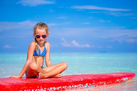 petite fille maillot de bain: Adorable petite fille sur une planche de surf dans la mer turquoise Banque d'images