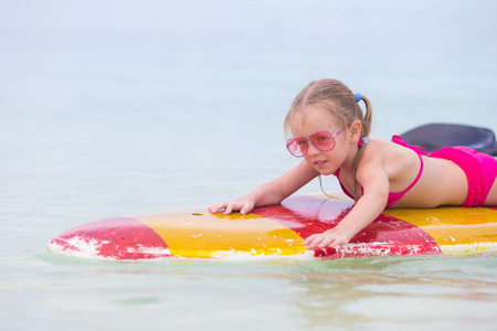 child swimsuit: Little adorable girl on a surfboard in the turquoise sea Stock Photo