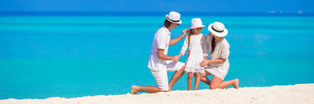 Young family on white beach during summer vacation photo