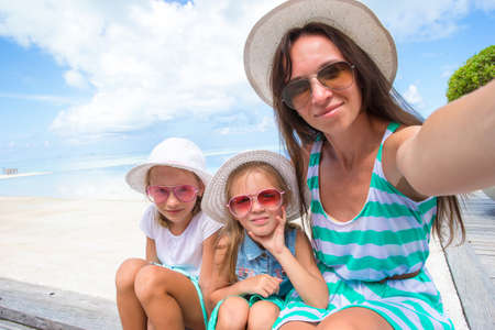 Mother and little girls taking selfie at tropical beach photo