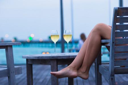 vino: Mujer joven con un vaso de vino blanco en la noche