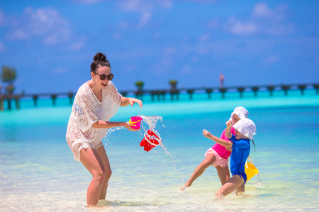 vacation: Young mom and little girls having fun during summer beach vacation Stock Photo