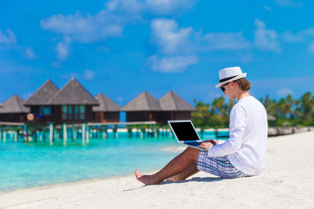 Young man with laptop at tropical beach near water villa Archivio Fotografico
