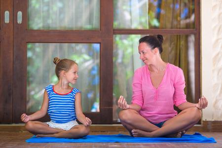 position d amour: Jeune femme et petite fille faisant du yoga exercice en plein air sur la terrasse