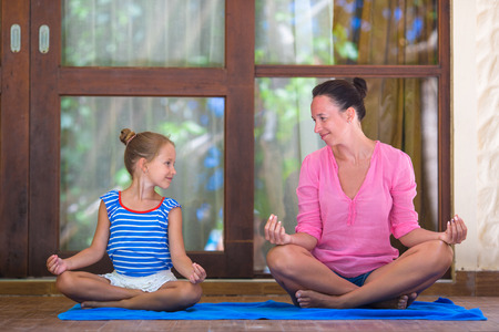 Young woman and little girl doing yoga exercise outdoor on terrace