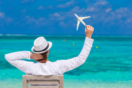 Young man with miniature of an airplane at tropical beach photo