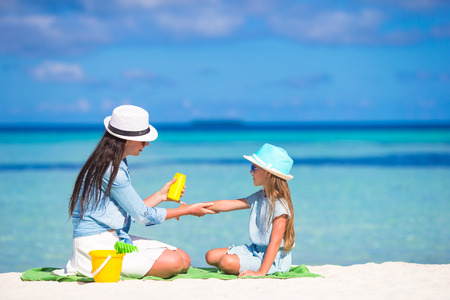 sunscreen: Young mother applying sunscreen on her kid
