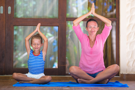 yoga meditation: Young woman and little girl doing yoga exercise outdoor on terrace