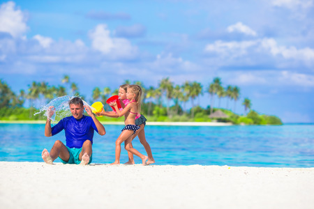 Adorable little girls having fun with dad on white beach photo